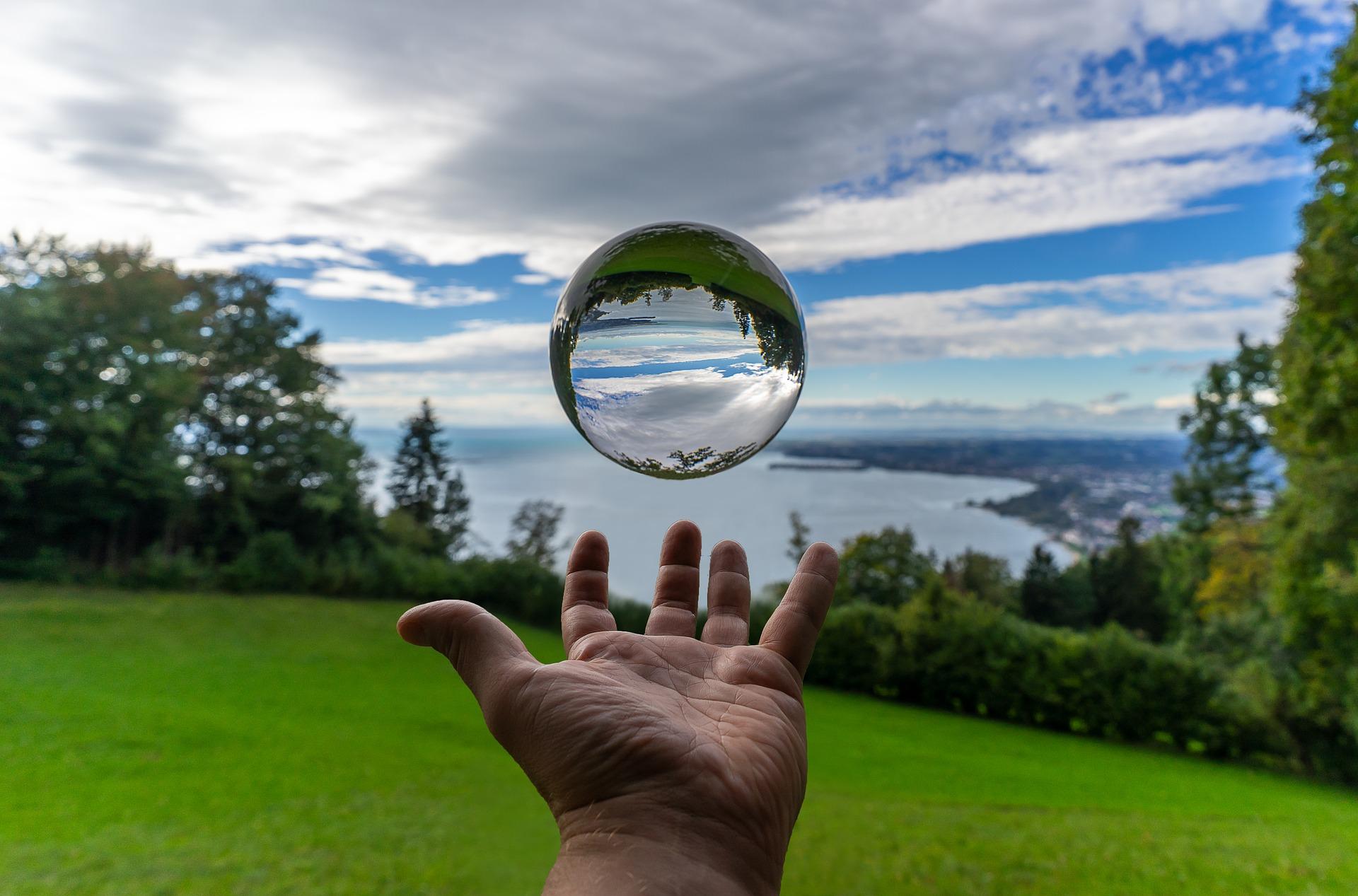 Hand hält Glaskugel überm Bodensee